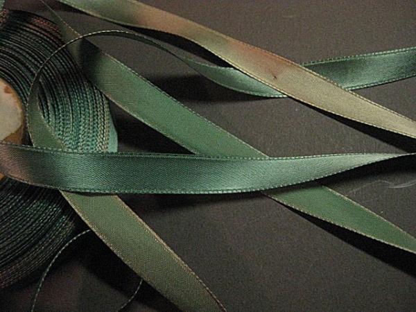 Teal satin rayon ribbon is faded